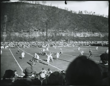 The high school's football team takes on an unidentified opponent. View from the bleachers show spectators lining the field on all sides.