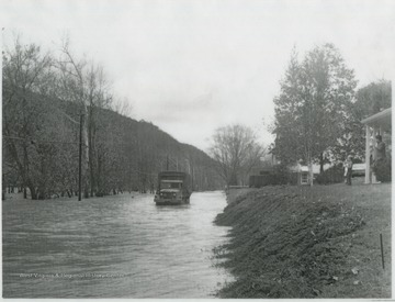 A United States National Guard truck attempts to make its way across the flooded Greenbrier Drive as a young boy and man watch from their home above. Subjects unidentified.