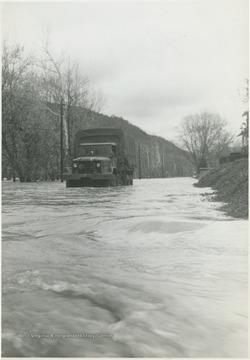 Flood waters surge toward the truck as it attempts to make its way across the road.