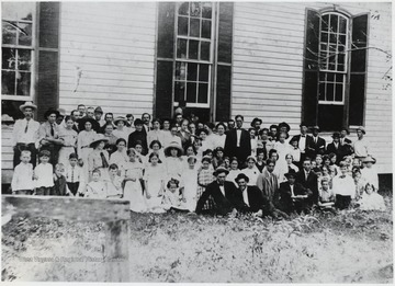 A group poses outside of the church building.