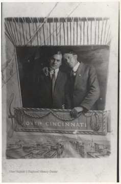 "Hartley, left, and Kiser, right, pose behind a cut-out that makes them appear as if they were in a hot air ballon. The banner on the poster reads, ""Over Cincinnati"". Hartley was a C & O Railroad train dispatcher and Kiser was a telegraph operator."