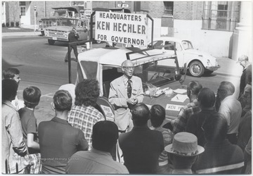 Hechler campaigning for governor on the corner of 2nd Avenue and Temple Street. A crowd surrounds him as he speaks.