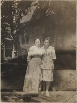 Keatley, to the left, is the wife of Sheriff Keatley. The two women stand on the sidewalk outside a home.