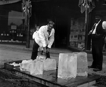 The Ice Man chips apart large blocks of ice.