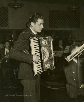 """Tony Biacco, steelmaker from Yorkville possesses two strong hands with which he capably handles ductillite and his accordion. His appearances on the family broadcast have been highly commendable. Now a regular in orchestra in 1943."""