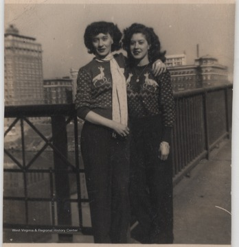Ruth Smith Norris (left) and Eula Mae Garten (right) pose in Christmas sweaters with the city in the background.