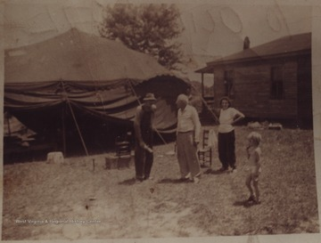 Two men, a woman and a child stand outside the large tent set up for movie watching. Subjects unidentified.