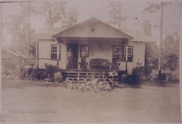 Two men stand outside on the porch of the C. C. C. camp building which is located near Pinecrest Sanitarium. Subjects unidentified.