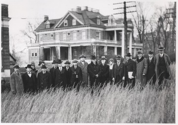 A group of unidentified men stand in a field that will become the Hall of Chemistry. In the background is the Purinton House.