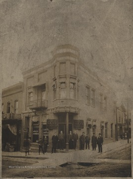 A group of men are pictured outside the building. Subjects unidentified. There appears to be construction underway on the street in front of the bank.