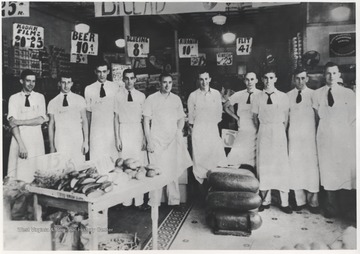 A group of grocer employees pose inside the first ever Kroger inside of Hinton, located on 3rd Avenue. Later, this store turned into the Bowlings Dairy Bar. Subjects unidentified.