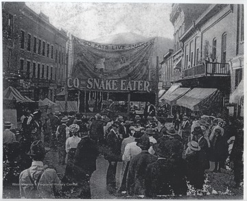 A group of men gather outside a tent where a man supposedly eats live snakes. View looking down from Temple Street toward Summers Street.