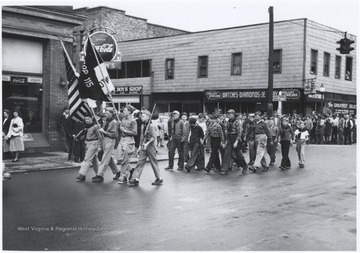 Four boys in their Boy Scout uniforms lead their troop down the street. Subjects unidentified.