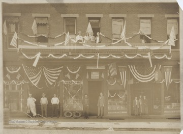 From left to right is the Hardware Store, Bell Telephone Business Office, Watt's Studio, and Sutherland Jewelry on 3rd Avenue. The store owners and clerks pose outside of their respective places. Subjects unidentified.