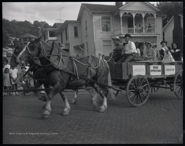 "People dressed in old fashioned clothing are pulled down the street in a wagon by two horses. Signs on the cart read, ""Health"", ""Home Improvement"", and ""Education."" Subjects unidentified."