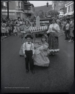 A young boy and girl pose in front of two older women in the middle of the street. They are dressed in old-fashioned attire to reflect the style of 1863. Spectators watch from the sidewalks. Subjects unidentified.