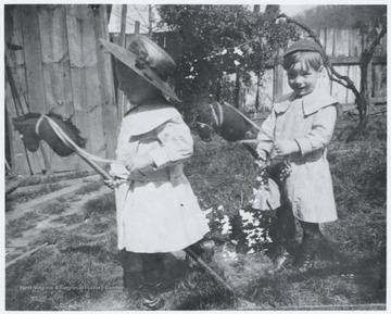 The two children play outside with stick horses. The yard is attached to the John Flanagan and R.O. Murrell home located on the corner of 5th Avenue and Summers Street.