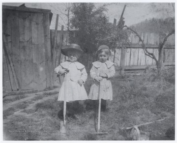 The two children play outside with yard tools. The yard is attached to the John Flanagan and R.O. Murrell home located on the corner of 5th Avenue and Summers Street.