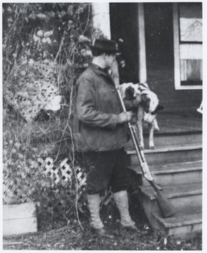 Murrell holds a rifle next to his pets outside of the Flanagan-Murrell home located on the corner of 5th Avenue and Summers Street.