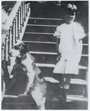 "Child of Robert Murrell stands beside the Murrell dog, ""Sport"", on the house steps. The home is located on the corner of 5th Avenue and Summers Street."