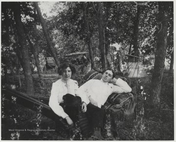 The Murrells are pictured somewhere in Summers County on a hammock resting between trees. In the background, multiple horse-drawn carriages are pictured.