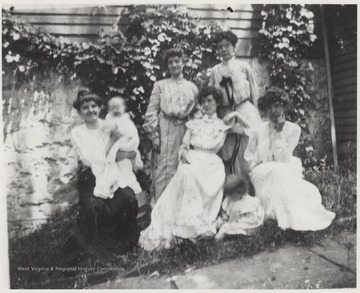Mrs. Robert Murrell is seated on the far right. An unidentified woman is holding Mildred Murrell. Young Bob Murrell is pictured sitting in the yard. The house is located on the corner of Summers Street and 5th Avenue.