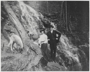 Bob Murrell, his wife and dogs are pictured beside a waterfall in an unknown location within Summers County.
