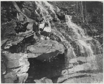 Mr. and Mrs. Robert Murrell, accompanied with an unidentified associate, pose beside the waterfall on a bed of rocks.