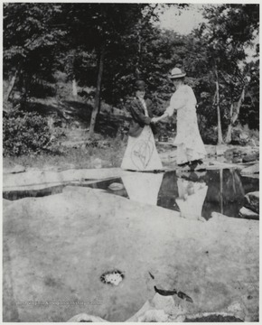 Murrell, right, holds the hand of an unidentified associate, perhaps helping her over the rocks.