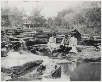 Bob Murrell busies himself by placing sticks into the water while his wife, seated on the right, watches.