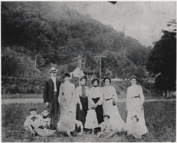 Mrs. Robert Murrell, pictured third from right, poses with members of the Faulkner family. A home are pictured in the background.