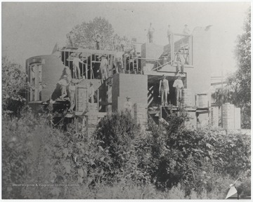 A group of men work on the building's construction. Subjects unidentified.