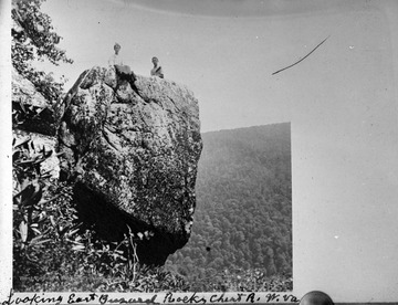 Two boys are pictured on top of the rock, looking east. Subjects unidentified.