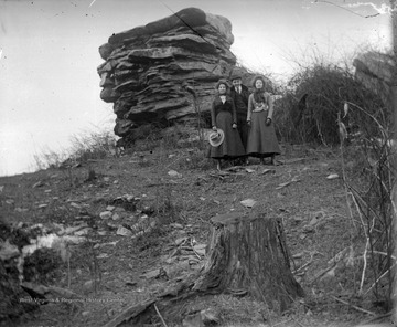 Two women and a man are pictured beside the rock formation, formally known as Dorsey's Knob. Subjects unidentified.