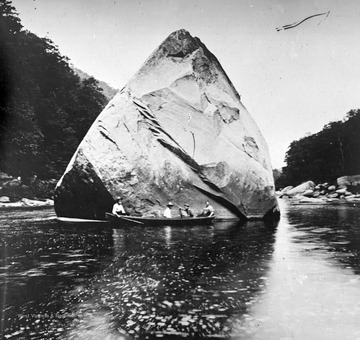 Four men sit in a canoe beside the large boulder in the middle of the river. Subjects unidentified.