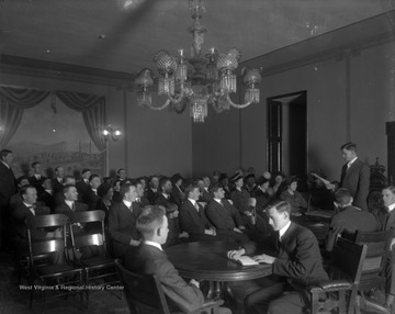 A group of students are gathered in a room. Many are listening to a man who is standing and reading from a sheet of paper. Subjects unidentified.