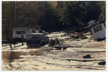 An unidentified man stands next to a car and several houses that were flooded when a stream, possibly Seneca Creek or White's Run, changed it's course during the 1985 flood in the area around Parsons, Elkins, Onego, and Mounth of Seneca, W. Va.