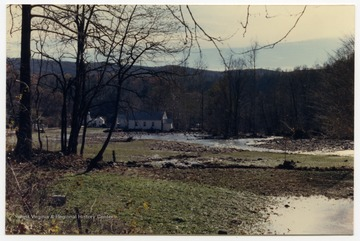 A church in Onego, W. Va. is surrounded by water from a creek that used to be behind it.  The flooded and muddy field was previously a green pasture. The damage occurred during the November 1985 flood in the area around Parsons, Elkins, Onego, and Mounth of Seneca, W. Va.