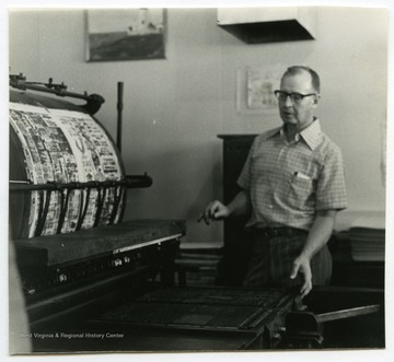 "Woodrow ""Woody"" Wilson, owner of the Wirt County Journal in Elizabeth, W. Va., next to the linotype machine used for the newspaper.The photos in this collection were used in chapters that appeared in Mountain Trace, a publication of Parkersburg High School in West Virginia, edited by Kenneth G. Gilbert."