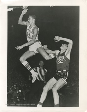 West, left, flies past Louisville's John Turner during the 1959 NCAA Semi-Finals. The Mountaineers won this game 93-78, with 38 points scored by West alone.