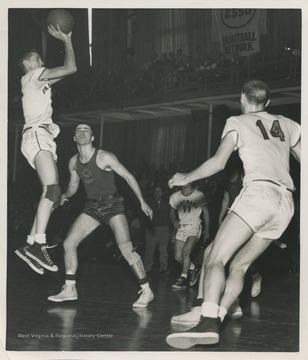 West, who is mid-air and ready to shoot the ball, played for East Bank High School as the team's starting small forward. He was named All-State from 1954–56, then All-American in 1956 when he was West Virginia Player of the Year, becoming the state's first high-school player to score more than 900 points in a season.