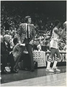 West, wearing a patterned blazer, with Jack McCloskey, left, look out onto the court as the game progresses. After fourteen years of playing for the team, West rejoined the Lakers as coach for three seasons between 1976 and 1982. He led the team to the playoffs each season.