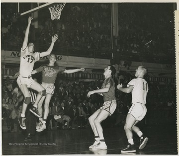 East Bank High School's Gary Stover, No. 17, drives in for a layup while Mullens High School's Gene Miller tries to halt the play. Also pictured is Mullens player Ronnie Cook and East Bank player Jack Landers, No. 11.Jerry West was also a player in this game and led the team to victory. The 1956 team secured the first ever state championship title for East Bank High School's basketball team.West was East Bank High School's starting small forward. He was named All-State from 1953–56, then All-American in 1956 when he was West Virginia Player of the Year, becoming the state's first high-school player to score more than 900 points in a season.