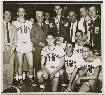 A portrait of the team, coached by Roy E. Williams. Jerry West is pictured in the center holding the trophy. The 1956 team secured the first ever state championship title for East Bank High School's basketball team.West was the team's starting small forward. He was named All-State from 1953–56, then All-American in 1956 when he was West Virginia Player of the Year, becoming the state's first high-school player to score more than 900 points in a season.