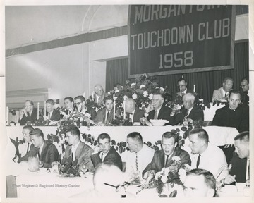A group of men are gathered at a spring banquet held at Hotel Morgan after the West Virginia University basketball team was ranked No. 1 in the United States.In the front row, from left to right, is unidentified, Jerry West, Bobby Joe Smith, Ronnie Retton, Bucky Bolyard, Butch Gude, Jim Warren, and possibly Willie Akers.In the second row, from left to right, is athletic director Red Brown, basketball referee Red Mahalic, Jody Gardner, Loyd Sherer, Don Vincent, Whitie Guyme, team physician Dr. Sam Morris, Golf-pro Reggie Spencer, and Father Scott.In the third row, from left to right, is University of Pittsburgh basketball coach Doc Cartson, WVU head coach Fred Schaus, unidentified, the team's general manager Mr. Gwair, and unidentified.