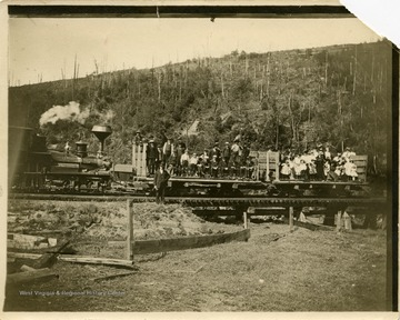 This image is part of the Thompson Family of Canaan Valley Collection. The Thompson family played a large role in the timber industry of Tucker County during the 1800s, and later prospered in the region as farmers, business owners, and prominent members of the Canaan Valley community.A group out for a Sunday picnic, near Davis poses with the train.