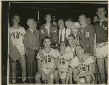 Jerry West, pictured holding the trophy, poses with his East Bank High School basketball team after winning the state championship. West led his team as the starting small forward. He was named All-State from 1953–56, then All-American in 1956 when he was West Virginia Player of the Year, becoming the state's first high-school player to score more than 900 points in a season.West was born in Cheylan, W. Va. in 1938. After high school, he went on to play basketball for West Virginia University and then rose to fame as a player for the Los Angeles Lakers of the NBA before becoming a basketball coach and manager.