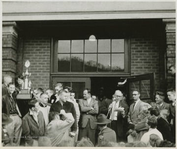 A crowd celebrates the victory in front of the East Bank High School building. Jerry West is pictured in a striped shirt, standing beside a boy holding the trophy on the left of the photograph.West led the East Bank High School basketball team to its first ever West Virginia state championship title. He was named All-State from 1953–56, then All-American in 1956 when he was West Virginia Player of the Year, becoming the state's first high-school player to score more than 900 points in a season.West was born in Cheylan, W. Va. in 1938. After high school, he went on to play basketball for West Virginia University and then rose to fame as a player for the Los Angeles Lakers of the NBA before becoming a basketball coach and manager.