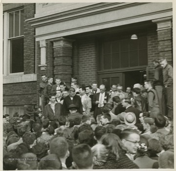 A crowd celebrates the victory in front of East Bank High School.Jerry West led the East Bank High School basketball team to its first ever West Virginia state championship title. He was named All-State from 1953–56, then All-American in 1956 when he was West Virginia Player of the Year, becoming the state's first high-school player to score more than 900 points in a season.West was born in Cheylan, W. Va. in 1938. After high school, he went on to play basketball for West Virginia University and then rose to fame as a player for the Los Angeles Lakers of the NBA before becoming a basketball coach and manager.