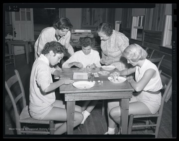 Two women supervise as three young girls paint bracelets. Subjects unidentified.